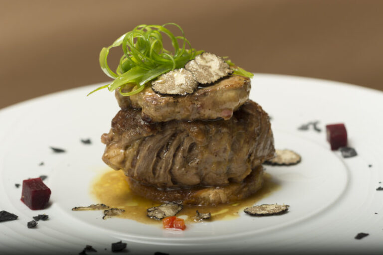 Sliced truffles topped on a grilled steak,  beef and pork,  with vegetable and sauce,  on a white plate,  brown background